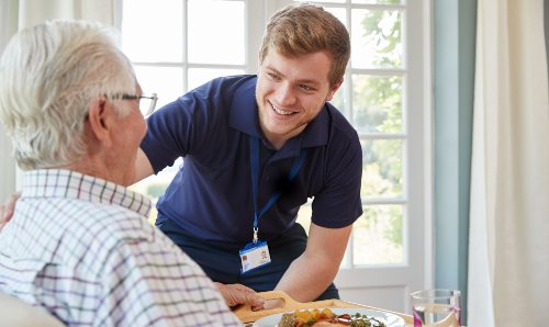 A male medical professional smiling at an elderly man.