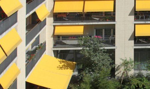 A block of flats with yellow canopies over the balconies.