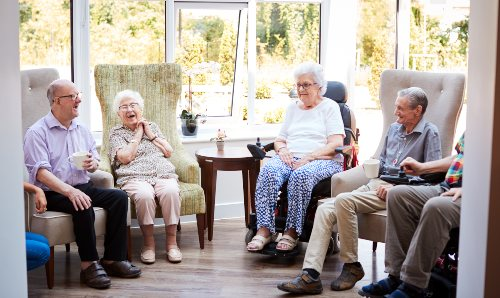 A group of elderly male and female people sat in a care home talking.
