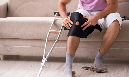 Someone's knee with a brace on it sat next to a crutch.