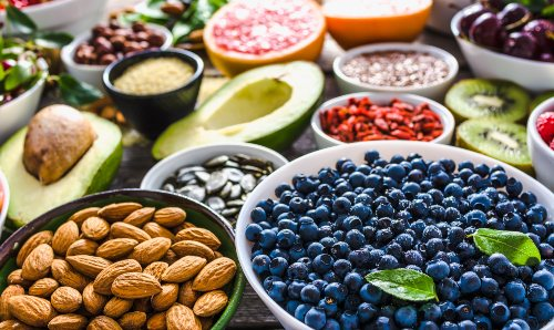 Bowls of healthy food including blueberries, almonds and avocado.