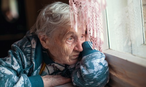 An older woman looking sad out of a window.